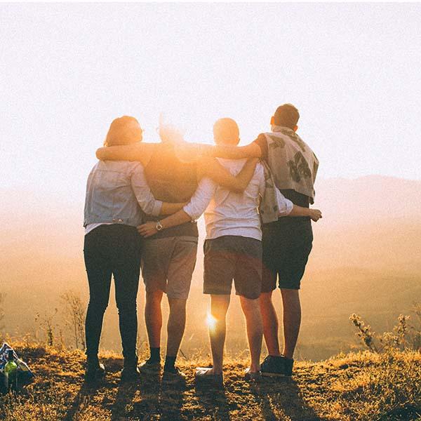 persone si abbracciano guardando il sole