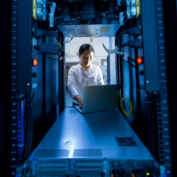 Asian female network administrator using laptop computer at networking rack cabinet on working in data center room