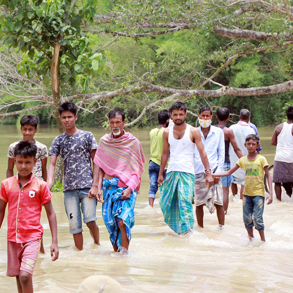 Nagaon, Assam / India - May 30 2020: People wades the flood water submerged road in Assam, India