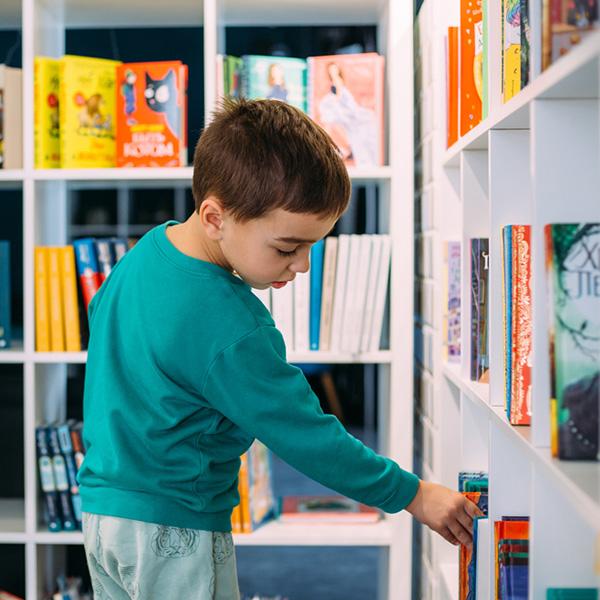 A little boy reaches for shelf of children